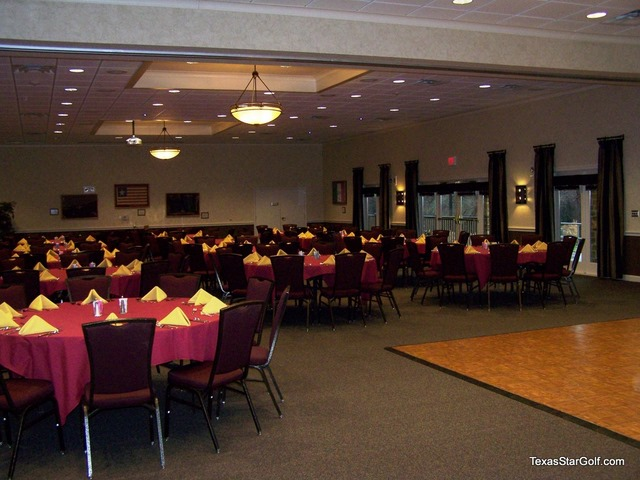 Room set with red tablecloths and stage/dancefloor