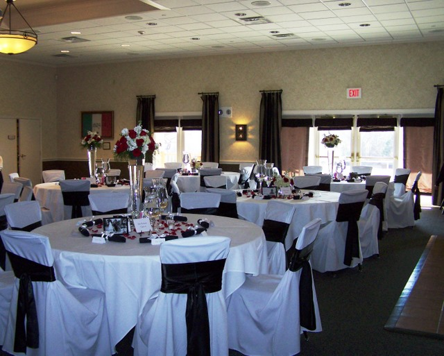Tables and chairs with white drapery and centerpieces