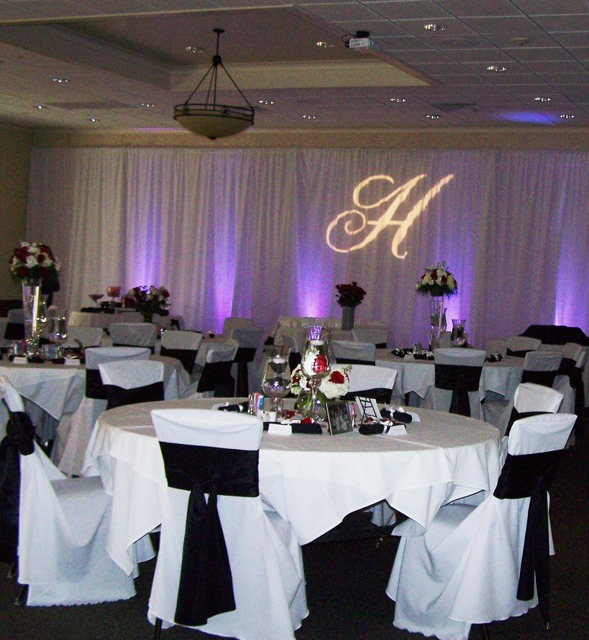 Tables and chairs with white drapery and cursive H projected on wall